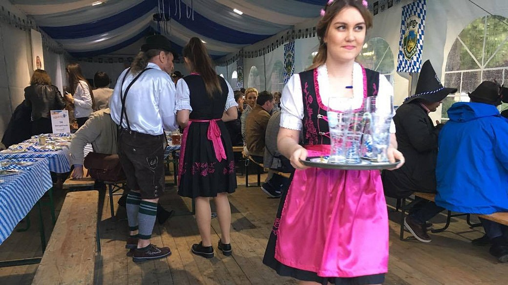 Bierfass, im Hintergrund: tanzenes Paar in bayerischer Tracht