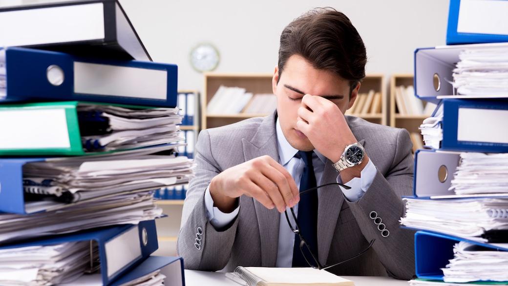 Bürokratie - überforderter Unternehmer zwischen Papierstapeln
